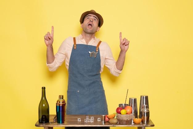 Barista maschio vista frontale davanti al tavolo con bevande e shaker sul muro giallo notte alcol maschio drink club bar
