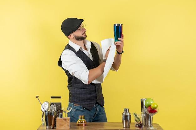 Barista maschio vista frontale davanti al tavolo con shaker pulizia shaker sulla parete gialla bar alcol night club bevanda giovanile