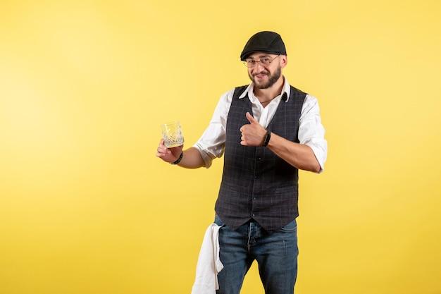 전면 보기 남성 바텐더 노란색 벽에 유리를 들고 알코올 작업 클럽 바 밤 남성
