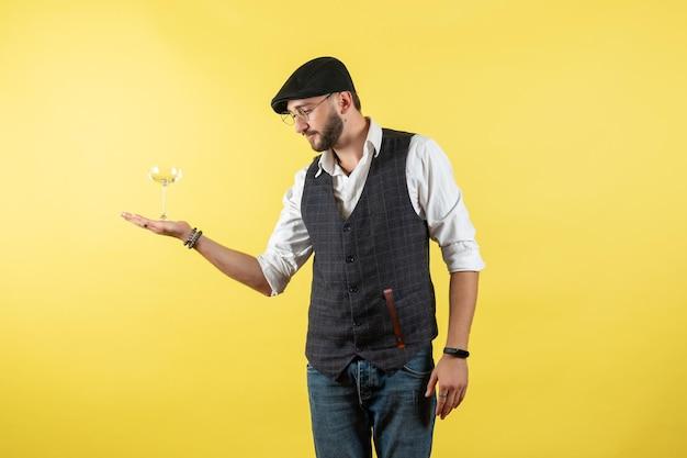 전면 보기 남성 바텐더 노란색 벽에 유리를 들고 남성 음주 알코올 나이트 클럽 바 작업