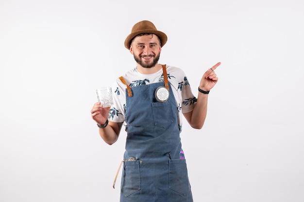 Vista frontale barista maschio che tiene il bicchiere sul muro bianco alcol club night drink lavoro modello bar nut