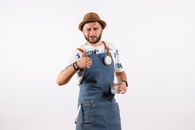 Vista frontale barista maschio che tiene il bicchiere su un muro bianco alcol lavoro club night drink bar nut