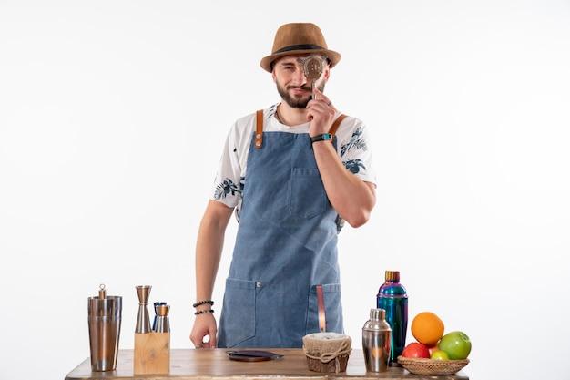 Barista maschio di vista frontale che tiene schiaccianoci sulla parete bianca chiara lavoro bar alcol club night drink service
