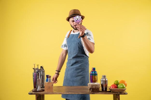 Vista frontale barista maschio che tiene schiaccianoci sul muro giallo club notte bar alcol bere lavoro colore