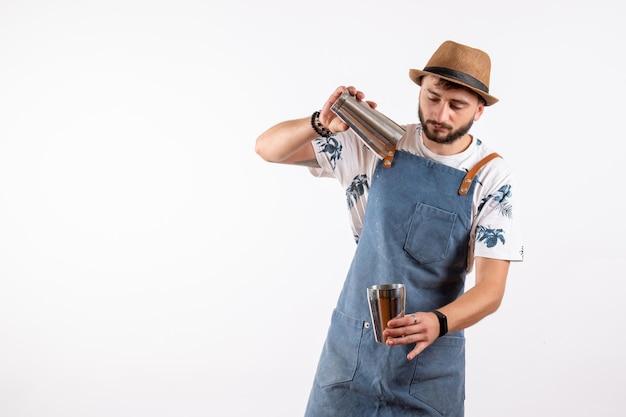 正面図男性バーテンダーがシェーカーを保持し、白い壁のクラブのナイトバーで飲み物を作るアルコール飲料の仕事の色