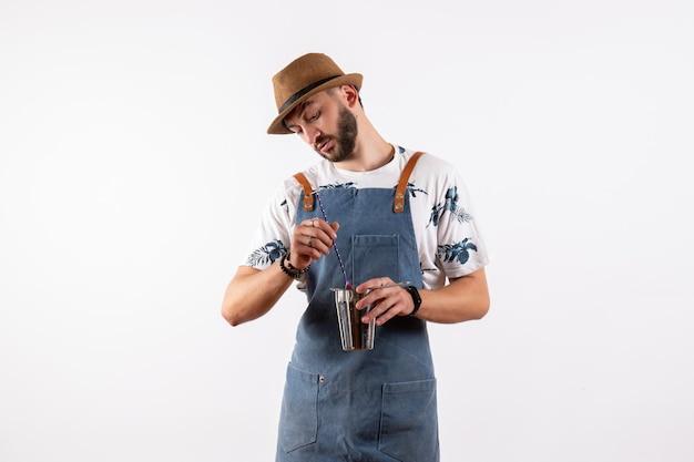 Вид спереди мужской бармен, держащий шейкер на белой стене, ночной клуб, алкогольные напитки, цветная полоса