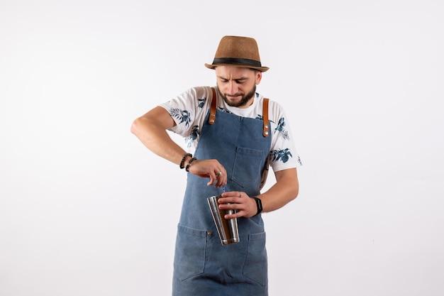 白い壁のクラブの夜の仕事のアルコールバーの飲み物にシェーカーを保持している正面図の男性バーテンダー