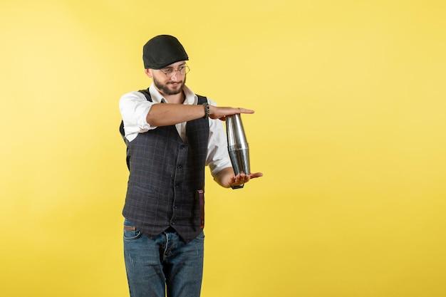 Vista frontale barista maschio che tiene shaker d'argento sulla parete gialla bere lavoro club alcol maschio bar notte