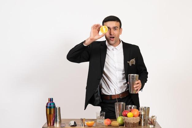Вид спереди мужчина-бармен в классическом костюме делает напиток на белой стене в ночном клубе, мужской бар, танцевальные напитки