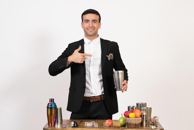 Вид спереди мужчина-бармен в классическом костюме делает напиток на белой стене, ночные напитки, клуб, мужской бар, танец