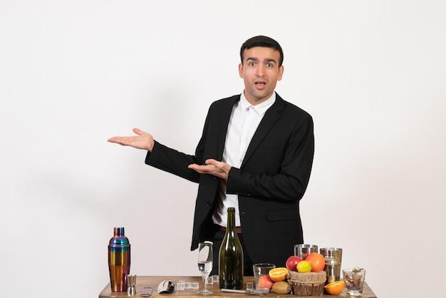 Вид спереди мужчина-бармен в классическом костюме, стоящий перед столом с напитками на белой стене, алкогольный бар, клуб, пить мужскую ночь