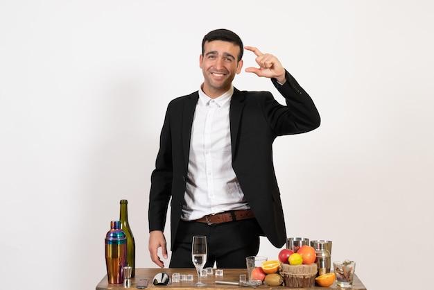 Вид спереди мужчина-бармен в классическом костюме, стоящий перед столом с напитками на белой стене, алкогольный клуб, напиток, мужской ночной бар