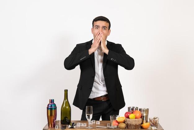 Вид спереди мужчина-бармен в классическом костюме, стоящий перед столом с напитками на белой стене, мужской ночной бар, пьет алкоголь