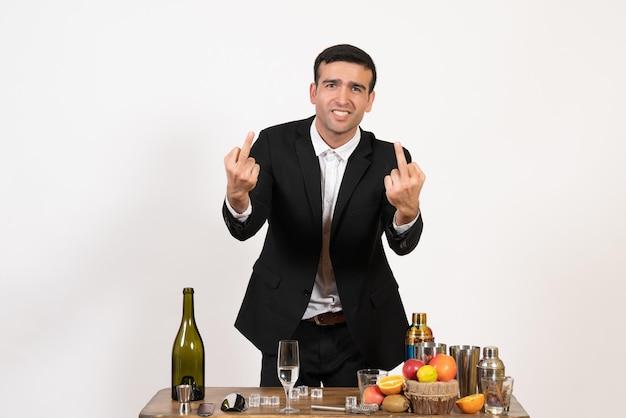 Вид спереди мужчина-бармен в классическом костюме, стоящий перед столом с напитками на белой стене, мужской алкогольный клуб, напиток, бар, ночь