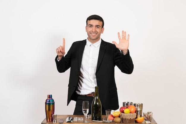 Вид спереди мужчина-бармен в классическом костюме, стоящий перед столом с напитками на светлой белой стене, алкогольный бар, клуб, пить мужскую ночь