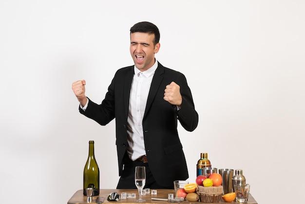 Вид спереди мужской бармен в классическом костюме, стоящий перед столом с напитками на белой стене, мужской алкогольный клуб, бар, ночной напиток