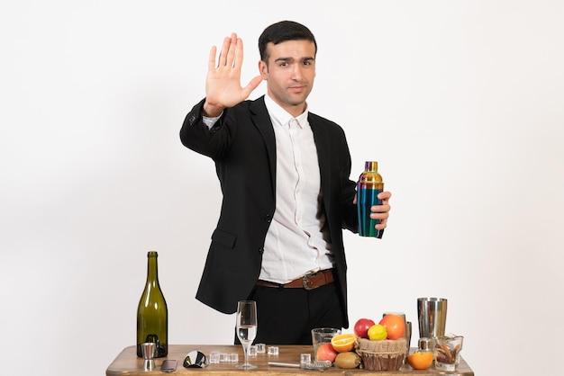 Вид спереди мужской бармен в классическом костюме, стоящий перед столом с напитками на белой стене, ночной мужской клуб, бар, алкогольный напиток