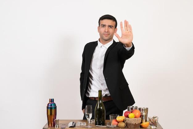 白い机の上に飲み物とテーブルの前に立っている古典的なスーツの正面図男性バーテンダーアルコールバークラブ飲み物男性の夜