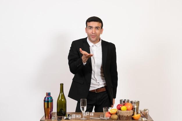Вид спереди мужской бармен в классическом костюме, стоящий перед столом с напитками на белом столе, мужской ночной бар, пьет алкоголь