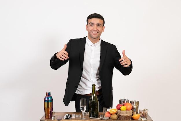 Вид спереди мужчина-бармен в классическом костюме, стоящий перед столом с напитками на белой стене, клубный алкогольный бар, пить мужскую ночь