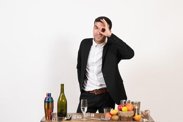 Вид спереди мужчина-бармен в классическом костюме, стоящий перед столом с напитками на белой стене, клубный алкоголь, мужской ночной бар, напиток