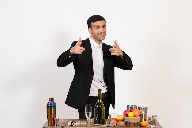 Вид спереди мужчина-бармен в классическом костюме, стоящий перед столом с напитками на белой стене, клуб, алкогольный ночной бар, напиток, мужчина