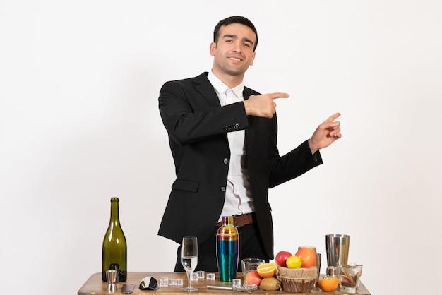 Вид спереди мужской бармен в классическом костюме, стоящий перед столом с напитками на белой стене, ночной мужской бар, алкогольный клуб