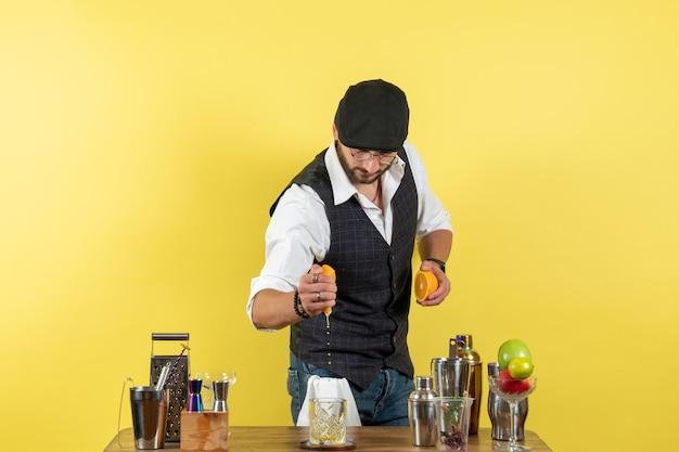 Вид спереди мужчина-бармен перед барной стойкой делает напиток на светло-желтой стене бар, ночной клуб алкогольных напитков