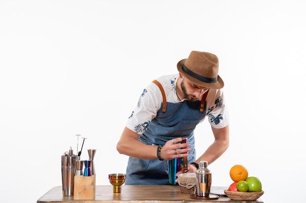 白い床のバーで飲み物を準備しているバーの机の前で正面図の男性バーテンダーアルコール夜の仕事フルーツドリンククラブ