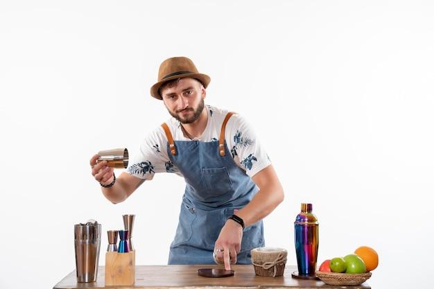 白い壁のバーで飲み物を準備しているバーデスクの前の正面図男性バーテンダーアルコール夜の仕事フルーツドリンククラブ