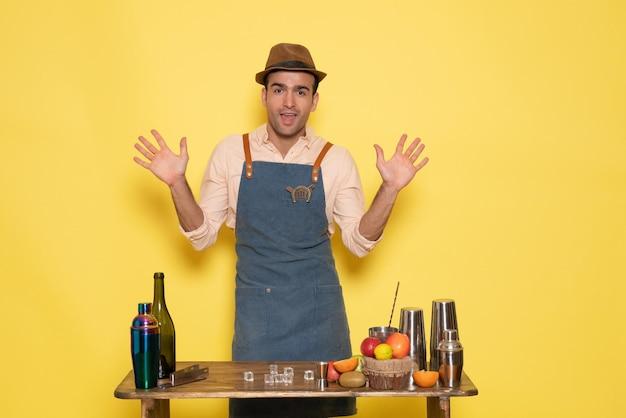 黄色い壁に飲み物と果物を持った机の前の正面図男性バーテンダードリンクバーナイトクラブジュース