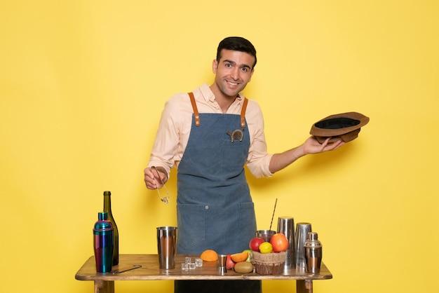 Вид спереди мужчина-бармен перед столом с шейкерами и бутылками, делающими напиток на желтой стене, клубный бар, пить ночной алкоголь
