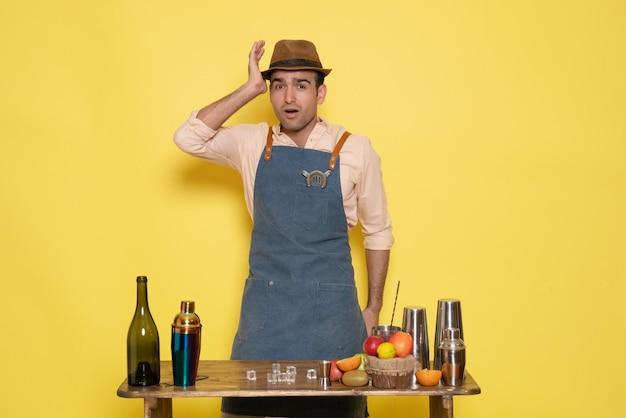Вид спереди мужчина-бармен перед столом с напитками и шейкерами на светло-желтой стене пить ночной алкогольный бар цветной клуб