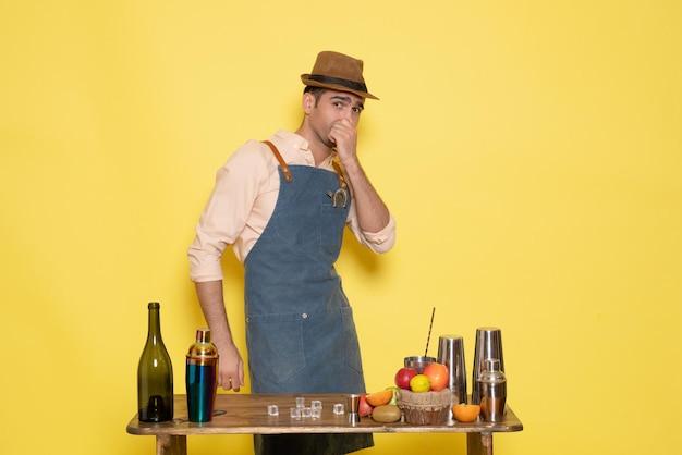 Вид спереди мужской бармен перед столом с напитками и шейкерами на желтой стене ночной алкоголь мужской клубный бар напиток