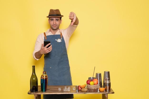 Вид спереди мужчина-бармен перед столом с напитками и шейкерами на желтом столе пить ночной алкогольный бар цветной клуб мужской