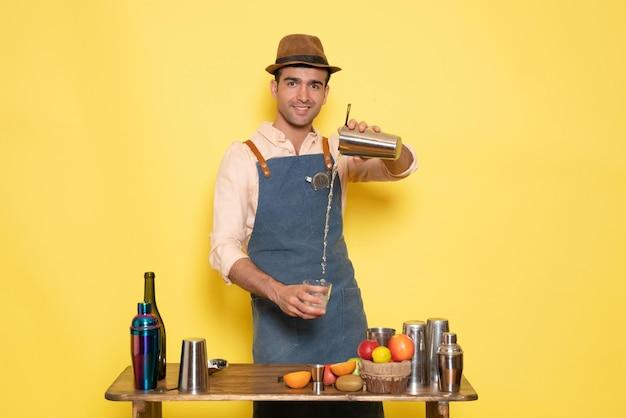 노란색 벽 클럽 바에서 음료를 만드는 셰이커와 병이 있는 탁자 앞에 있는 남성 바텐더는 야간 알코올을 마신다