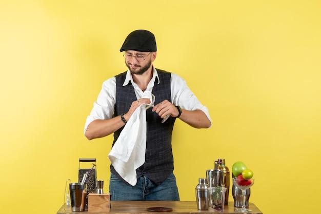 黄色い壁のバーでグラスを掃除するシェーカーとテーブルの前の正面図男性バーテンダーアルコールナイトユースドリンククラブ