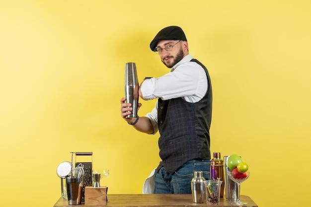Вид спереди мужчина-бармен перед столом с шейкерами, делающий напиток на желтой стене, алкогольный ночной клуб молодежных напитков