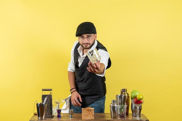 Вид спереди мужчина-бармен перед столом с шейкерами, готовящим напиток на желтой стене, алкогольный ночной молодежный клуб напитков