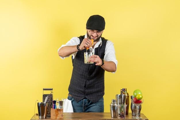 シェーカーが黄色い壁のバーでオレンジを絞って飲み物を準備しているテーブルの前の正面図男性バーテンダーアルコールナイトユースドリンククラブ