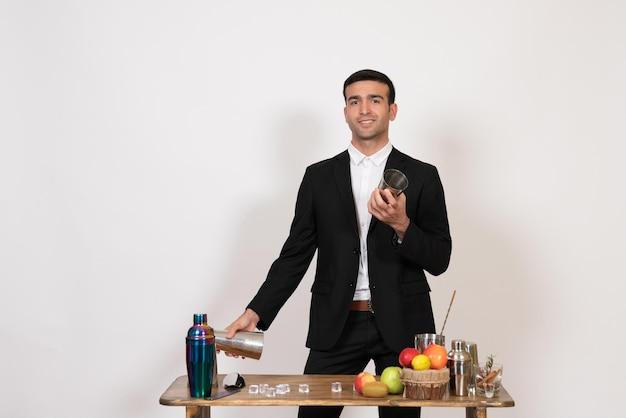 Вид спереди мужчина-бармен в костюме, стоящий перед столом с шейкерами и приготовляющий напиток на белой стене, мужской бар, ночной клуб, танцевальный напиток