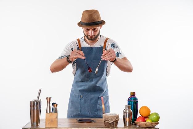 白い壁のバーの机の前で作業中の男性バーテンダーの正面図ジョブバーアルコールクラブナイトドリンクサービス