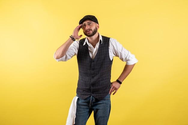 Barista maschio vista frontale solo in piedi e pensando sul muro giallo bere alcol lavoro night club maschio bar