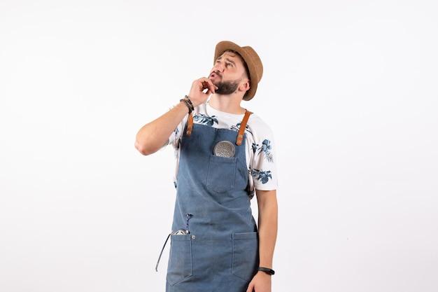 天井を見て、白い壁のアルコールジョブクラブの夜の飲み物バーナットを考えている正面図の男性バーテンダー