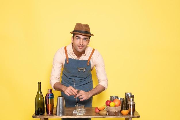 正面図男性バーテンダーが黄色い壁に飲み物を作る夜の飲み物アルコールバークラブ男性