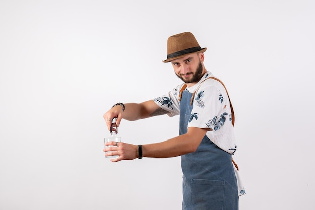 Barista maschio vista frontale che fa un drink sul muro bianco night job club alcol beve color bar