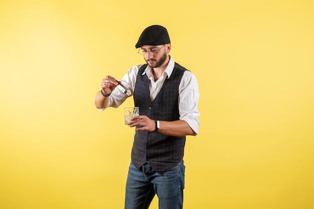 Barista maschio vista frontale che fa drink con cubetti di ghiaccio sulla parete gialla bere alcol lavoro night club maschio bar