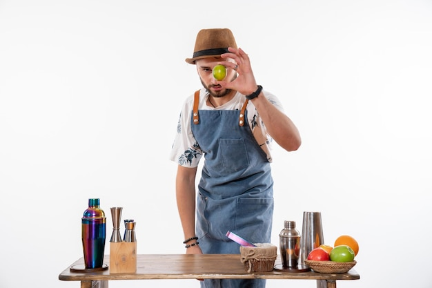 Front view male bartender making a drink and working with fruits on the white wall night bar alcohol club drink job