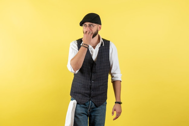 Barista maschio vista frontale che pensa nervosamente sul modello notturno della parete gialla bere lavoro club lavoro maschio