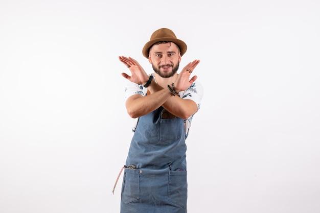 Barista maschio di vista frontale che posa con le sue mani sul modello di lavoro della bevanda di notte del club del bar dell'alcool della parete bianca